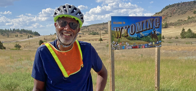 Photo of Scott Edwards in bicycle attire in front of Wyoming sign with hills in background